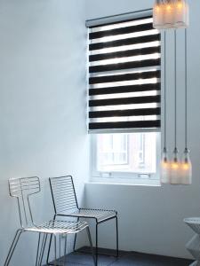 Duorolgordijn zwart met lichtinval en geen doorkijk in wachtkamer.