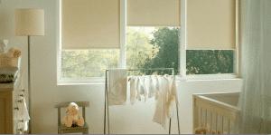 Verduisterende ivoorkleurige rolgordijnen in de babykamer voor een goede nachtrust