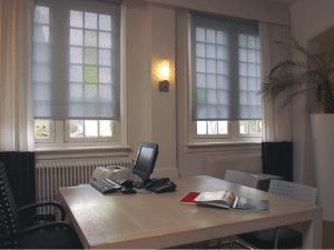 2x semi transparant rolgordijn grijs in kantoor.