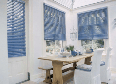 Brede licht-blauw jaloezieën in landelijke eetkamer.