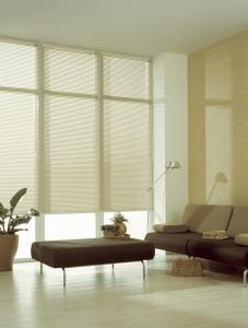 Zandkleurige jaloezieen in woonkamer geven een ruimtelijk effect.
