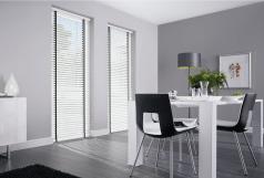 witte aluminium jaloezie met zwart ladderband in woonkamer.