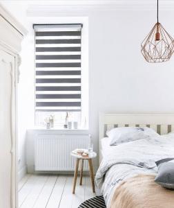 Duorolgordijn in lichte slaapkamer