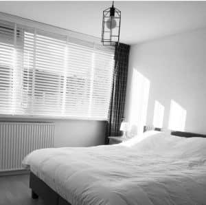 Slaapkamer met mooie witte houten jaloezieen.