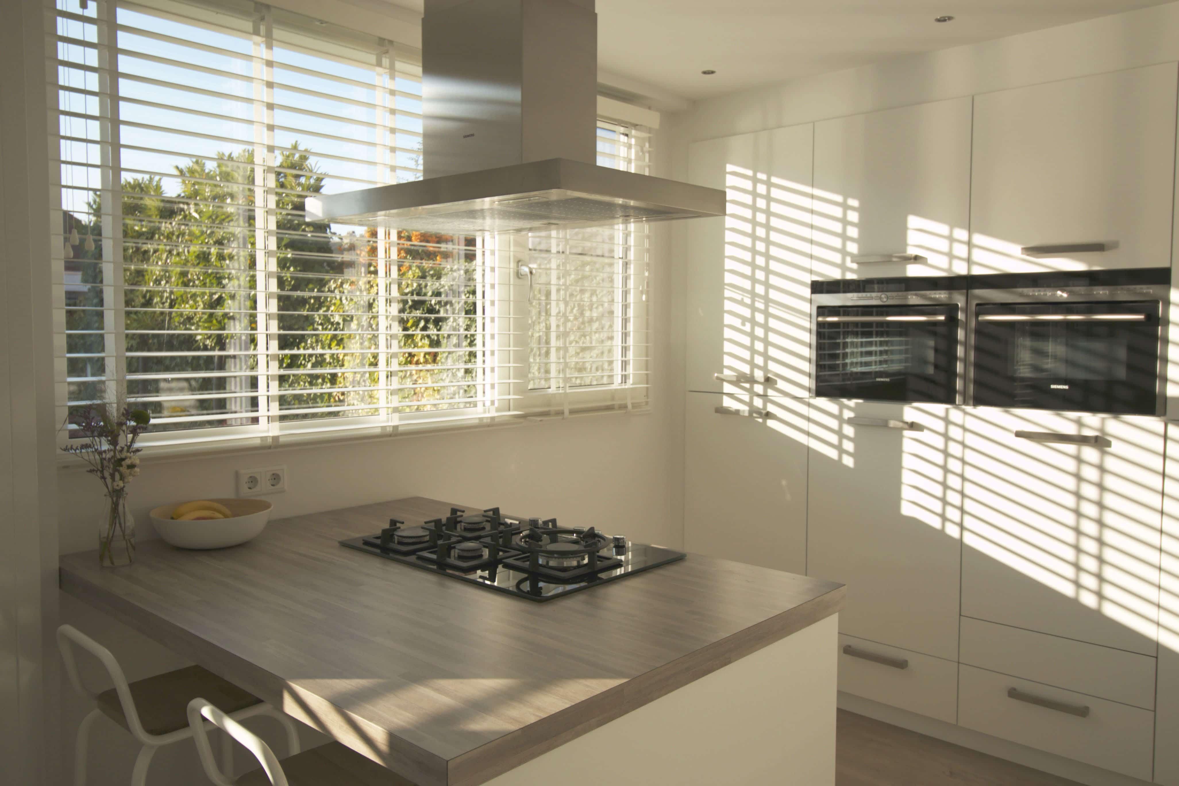 Keuken met houten jaloezieen wit en houten keukenblad