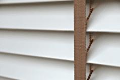 witte houten jaloezie met bruin ladderband