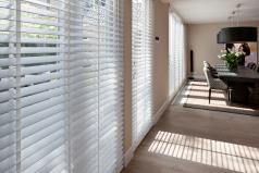 50 mm houten jaloezieen in de woonkamer voor een optimale lichtinval.