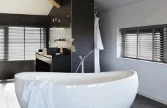 Jasno houten jaloezieen zijn ook geschikt voor in de badkamer.
