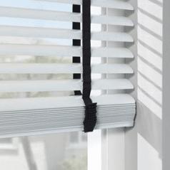Witte aluminium jaloezie 50mm met ladderband. Zie de lichtinval op de muur.