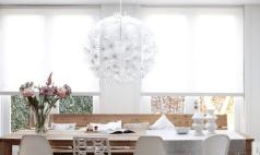 Witte rolgordijnen met lichtinval bij robuuste houten eettafel en verschillende stoel voor een stoer en ruimtelijk effect.