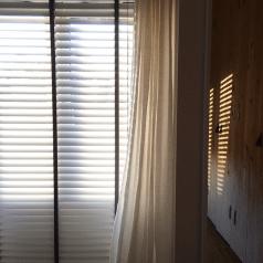 Zilveren aluminium jaloezie met zwart ladderband voor een fijne lichtinval in de slaapkamer.
