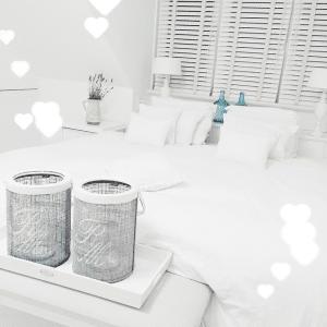 Romantische slaapkamer met witte houten jaloezieen