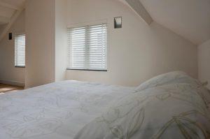 slaapkamer met houten jaloezieen