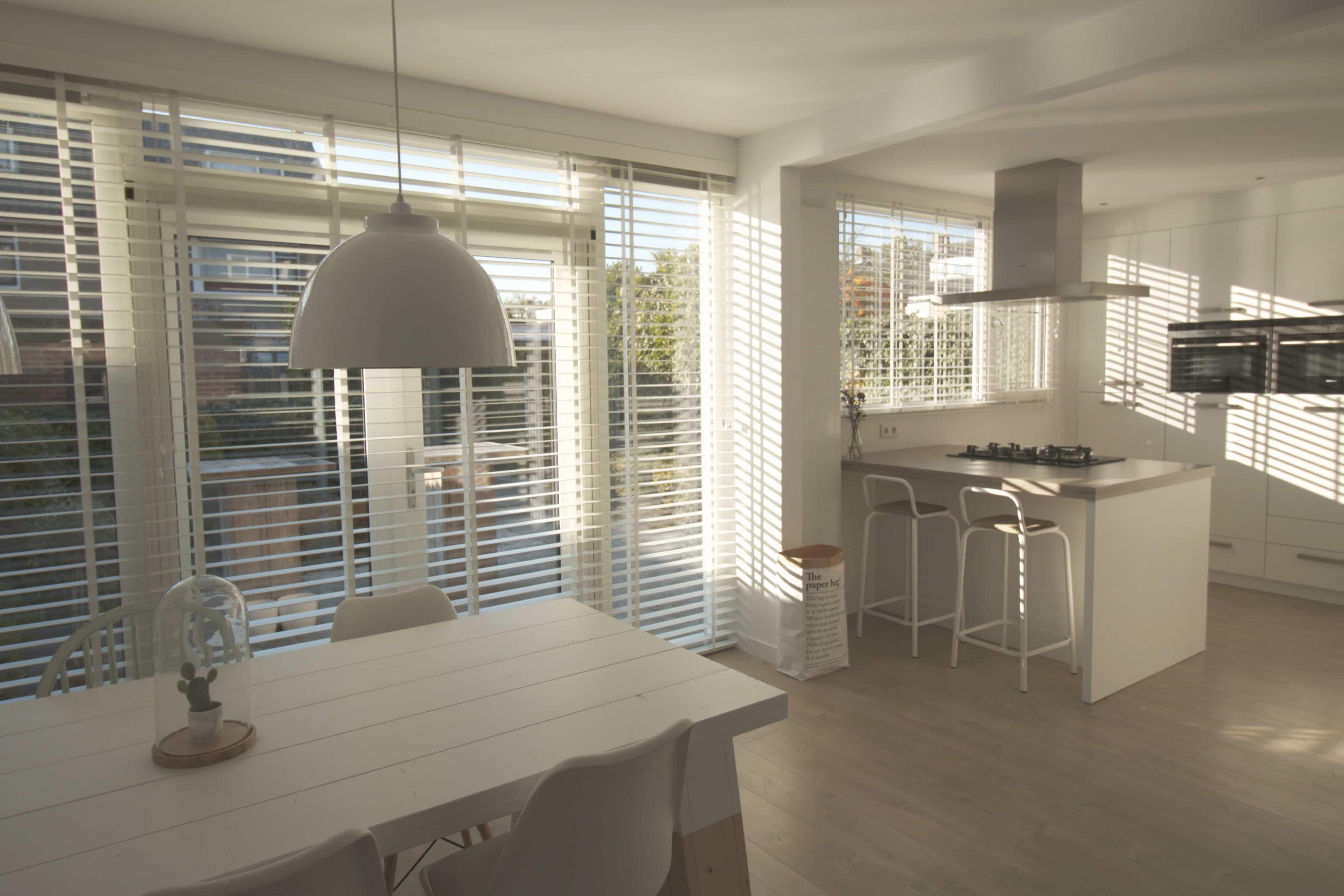 Woonkamer met eettafel keuken en houten jaloezieen wit
