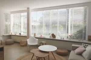 Woonkamer met grote ramen voor houten jaloezieen
